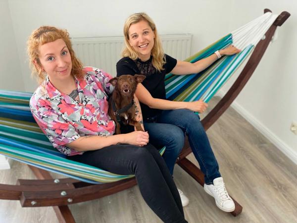 Julia und Kathleen mit Hund Milo auf einer Hängematte sitzend